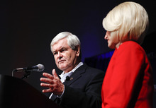 Republican presidential candidate former House Speaker Newt Gingrich speaks during his caucus night rally as his wife Callista looks on in Des Moines, Iowa, Tuesday, Jan. 3, 2012. (AP Photo/Chris Carlson)