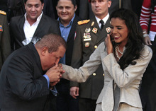Venezuela's President Hugo Chavez, left, plants a kiss on the hand of Miss World 2011 Ivian Sarcos after their meeting at the Miraflores presidential palace in Caracas, Venezuela, Wednesday Jan. 4, 2012. (AP Photo/Fernando Llano)