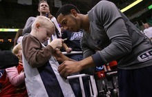 Steve Griffin  |  The Salt Lake Tribune  Utah Jazz guard Devin Harris signs a young fan's jersey following warm-up before game against the Bucks at EnergySolutions Arena in Salt Lake City, Utah  Tuesday, January 3, 2012.