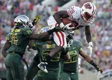 Wisconsin's Montee Ball (28) goes over Oregon's John Boyett (20) and others as he is stopped during the second half of the Rose Bowl NCAA college football game, Monday, Jan. 2, 2012, in Pasadena, Calif.  (AP Photo/Matt Sayles)