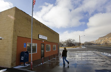 Al Hartmann     The Salt Lake Tribune An Emery resident enters the town's post office, which could close. Residents who do business and receive medications through the mail would have to drive north to Ferron to collect their mail.