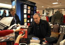 In this Dec. 13, 2011 photo, Jesus Esparza, right, of Chicago, shops at the Macy's on State Street store in Chicago. Many retailers are reporting solid sales gains for December, capping a decent holiday season. (AP Photo/Charles Rex Arbogast)