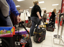 FILE - In this Nov. 25, 2011 file photo, customers wait in line to pay for their items at a Kohl's department store in La Habra, Calif. Many retailers are reporting solid sales gains for December, capping a decent holiday season. (AP Photo/Jae C. Hong, File)