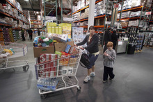 FILE - In this Dec. 8, 2011 file photo, Jenni Weber and her son Jacob, 7, of Portland, shop at a Costco store, in Portland, Ore. Costco Wholesale Corp.'s revenue at stores open at least a year rose 7 percent in December, narrowly missing Wall Street's expectations. (AP Photo/Rick Bowmer, File)
