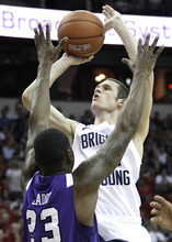 Brigham Young's Stephen Rogers, right, shoots over TCU's J.R. Cadot during the first half of an NCAA college basketball game in the second round of the Mountain West Conference tournament, Thursday, March 10, 2011, in Las Vegas. (AP Photo/Julie Jacobson)