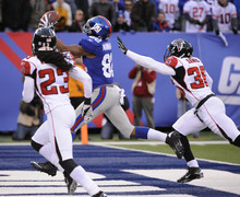 New York Giants wide receiver  Mario Manningham (82) catches a 27-yard touchdown pass against Atlanta Falcons cornerback Dunta Robinson (23) and AJames Sanders during the second half of an NFL wild card playoff football game Sunday, Jan. 8, 2012, in East Rutherford, N.J. (AP Photo/Bill Kostroun)
