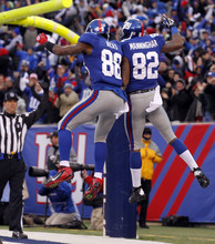 New York Giants wide receiver Mario Manningham (82) celebrates his 27-yard touchdown pass against Atlanta Falcons with teammate Hakeem Nicks during the second half of an NFL wild card playoff football game Sunday, Jan. 8, 2012, in East Rutherford, N.J. (AP Photo/Julio Cortez)