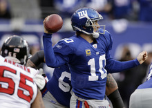 New York Giants quarterback Eli Manning (10) passes during the first half of an NFL wild card playoff football game Sunday, Jan. 8, 2012, in East Rutherford, N.J. Left is Atlanta Falcons defensive end John Abraham (55). (AP Photo/Matt Slocum)