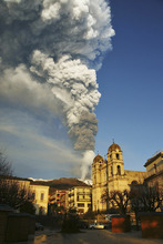 Smoke and ash billows from Mount Etna framed by the Sicilian town of Zafferana, near Catania, southern Italy, Thursday Jan. 5, 2012. The eruption of the Mount Etna volcano lasted a few hours and was the first in 2012. (AP Photo/Carmelo Imbesi)
