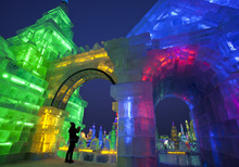 A woman takes picture of the colorful buildings made from blocks of ice during the opening ceremony of the Harbin International Ice and Snow festival in Harbin in northeastern's China's Heilongjiang province, Thursday, Jan. 5, 2012. (AP Photo/Andy Wong)