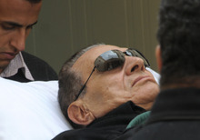 RETRANSMISSION FOR ALTERNATE CROP - Former Egyptian president Hosni Mubarak arrives by gurney to court in Cairo, Egypt, Thursday, Jan. 5, 2012. The prosecutor in the trial of Hosni Mubarak on Thursday demanded the death penalty for the ousted Egyptian leader on charges of complicity in the killing of protesters during last year's uprising against his rule. Mustafa Khater, one of a five-member prosecution team, also asked the judge for the death sentence for Mubarak's security chief and six top police commanders being tried in the same case.(AP Photo/Mohammed al-Law)