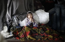 A young stranded passenger sits wrapped in a blanket at a bus station in Jammu, India, Saturday, Jan. 7, 2012. The Srinagar-Jammu national highway remained closed for the second consecutive day following heavy snowfall at many areas along the road. (AP Photo/Channi Anand)