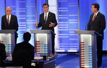 Elise Amendola  |  The Associated Press Former Massachusetts Gov. Mitt Romney, center, answers a question as Rep. Ron Paul, R-Texas, left, and former Pennsylvania Sen. Rick Santorum listen during a Republican presidential candidate debate at Saint Anselm College in Manchester, N.H., Saturday.