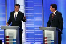 Elise Amendola  |  The Associated Press Former Massachusetts Gov. Mitt Romney, left, answers a question as former Pennsylvania Sen. Rick Santorum listens during a Republican presidential candidate debate at Saint Anselm College in Manchester, N.H., Saturday.