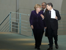 German Chancellor Angela Merkel, left, and French President Nicolas Sarkozy arrive for a news conference after talks about the Euro debt crisis at the chancellery in Berlin, Monday, Jan. 9, 2012. The French and German leaders stressed that they view boosting economic growth a priority as they push through with efforts to stem the eurozone's debt crisis. (AP Photo/Markus Schreiber)