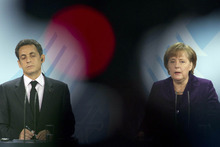 German Chancellor Angela Merkel, right, and French President Nicolas Sarkozy brief the media after talks about the Euro debt crisis at the chancellery in Berlin, Monday, Jan. 9, 2012. The French and German leaders stressed that they view boosting economic growth a priority as they push through with efforts to stem the eurozone's debt crisis. (AP Photo/Markus Schreiber)