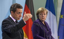 German Chancellor Angela Merkel, right, and French President Nicolas Sarkozy, left, stand next to each other during a news conference at the Chancellery in Berlin, Germany, Monday, Jan. 9, 2012. The French and German leaders stressed that they view boosting economic growth a priority as they push through with efforts to stem the eurozone's debt crisis. (AP Photo/Gero Breloer)