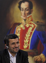 Iran's President Mahmoud Ahmadinejad gestures during a ceremony to sign agreements at Miraflores presidential palace, back dropped by a painting of Venezuela's independence hero Simon Bolivar in Caracas, Venezuela, Monday, Jan. 9, 2012. Ahmadinejad visited with Chavez as tensions rose with the U.S. over Tehran's nuclear program and a death sentence against an American man convicted of working for the CIA. Venezuela is the first leg of a four-nation tour that will also take Ahmadinejad to Nicaragua, Cuba and Ecuador. (AP Photo/Ariana Cubillos)