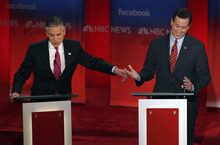 Former Utah Gov. Jon Huntsman, left, reaches for former Pennsylvania Sen. Rick Santorum during a Republican presidential candidate debate at the Capitol Center for the Arts in Concord, N.H., Sunday, Jan. 8, 2012. (AP Photo/Charles Krupa)