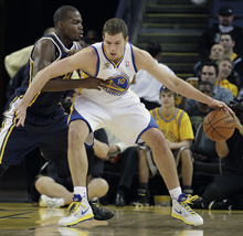 Golden State Warriors' David Lee, right, drives against Utah Jazz's Paul Millsap during the first half of an NBA basketball game Saturday, Jan. 7, 2012, in Oakland, Calif. (AP Photo/Ben Margot)