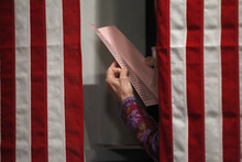 A resident reads over her ball ballots before the stoke of midnight when she can cast her voter in the first-in-the-nation presidential primary, at The Balsams Grand Resort, Monday, Jan. 9, 2012, in Dixville, N.H. (AP Photo/Matt Rourke)
