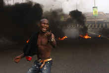 A angry youth protest in front of a burning barrier following the removal of a fuel subsidy by the government in Lagos, Nigeria, Tuesday, Jan. 10, 201. Angry youths erected a burning roadblock outside luxury enclaves in Nigeria's commercial capital Tuesday as a paralyzing national strike over fuel prices and government corruption entered its second day.(AP Photo/Sunday Alamba)