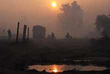 People make their way in the morning fog on the outskirts of Amritsar, India, Tuesday, Jan. 10, 2012. Though India is famous for its brutally hot summers, temperatures fall sharply for a few weeks in December and January. (AP Photo/Sanjeev Syal)