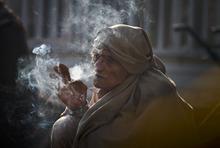 A Pakistani laborer smokes cigarette early morning as he waits for work at a roadside in Rawalpindi, Pakistan, Tuesday, Jan. 10, 2012. (AP Photo/Anjum Naveed)