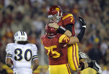 Southern California quarterback Matt Barkley (7) and offensive tackle Matt Kalil( 75) celebrate a touchdown by Rhett Ellison during the first half of an NCAA college football game against UCLA in Los Angeles, Saturday, Nov. 26, 2011. At left is UCLA linebacker Eric Kendricks. (AP Photo/Jae Hong)