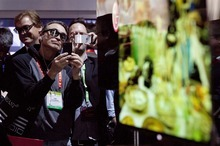 Julie Jacobson  |  The Associated Press Industry affiliates make photos of the new LG 55-inch OLED television at the International Consumer Electronics Show in Las Vegas.