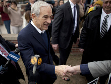 Republican presidential candidate, Texas Rep. Ron Paul shakes hands outside the Webster School in Manchester, N.H., Tuesday, Jan. 10, 2012, where primary voting was taking place.  (AP Photo/Evan Vucci)