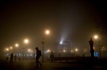People walk on Plaza del Castillo Square as the fog envelops the city, last night, in Pamplona, northern Spain, Thursday, Jan. 12, 2012. (AP Photo/Alvaro Barrientos)