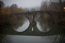 A man crosses the Magdalena bridge as low-lying cloud envelops the Arga River, near Pamplona, northern Spain, Thursday, Jan. 12, 2012. (AP Photo/Alvaro Barrientos)