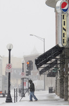 A man clears snow from a sidewalk in downtown Champaign, Ill., Thursday morning, Jan. 12, 2012. Many parts of Illinois were receiving their first significant snowfalls of the winter Thursday with anywhere from an inch to several inches expected. (AP Photo/David Mercer)