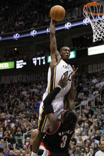 Utah Jazz forward Jeremy Evans (40) goes for a dunk over Portland Trail Blazers forward Gerald Wallace (3) during the second half of an NBA preseason basketball game Wednesday, Dec. 21, 2011, in Salt Lake City.  Evans was called for a charge on the play. Utah won 92-89. (AP Photo/Jim Urquhart)