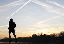 A man jogs to work at sunrise past the Serpentine lake in London's Hyde Park, Friday, Jan. 13, 2012. The Serpentine is the venue for some of the London 2012 Olympic Games events such as the Triathlon and Open Water swimming. (AP Photo/Alastair Grant)