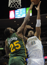 Jack Dempsey  |  The Associated Press Denver Nuggets center Nene (31) from Brazil shoots over Utah Jazz center Al Jefferson (25) during the first quarter of an NBA basketball game Sunday in Denver. The Jazz won, 106-96.
