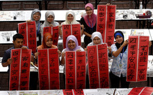 Malay teachers show off their calligraphy works after a Chinese calligraphy event in conjunction with the upcoming Chinese New Year of the Dragon at Tsun Jin High School in Kuala Lumpur, Malaysia, Saturday, Jan. 14, 2012. (AP Photo/Lai Seng Sin)