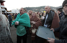 Passengers of the luxury ship that ran aground off the coast of Tuscany arrive on a ferry in Porto Santo Stefano, Italy, Saturday, Jan. 14, 2012. A luxury cruise ship ran aground off the coast of Tuscany, gashing open the hull and taking on water, forcing some 4,200 people aboard to evacuate aboard lifeboats to a nearby island early Saturday. At least three were dead, the Italian coast guard said. Three bodies were recovered from the sea, said Coast Guard Cmdr. Francesco Paolillo. (AP Photo/Gregorio Borgia)