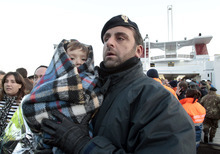 A police officer holds a baby wrapped in a blanket as passengers of the luxury ship Costa Concordia that ran aground off the coast of Tuscany arrive on a ferry in Porto Santo Stefano, Italy, Saturday, Jan. 14, 2012. The Costa Concordia ran aground, gashing open the hull and taking on water, forcing some 4,200 people aboard to evacuate aboard lifeboats to a nearby island early Saturday. (AP Photo/Gregorio Borgia)