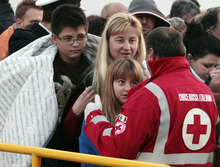 Passengers of the Costa Concordia, a luxury cruise ship that ran aground off the coast of Tuscany, arrive on a ferry in Porto Santo Stefano, Italy, Saturday, Jan. 14, 2012. The luxury cruise ship ran aground off the coast of Tuscany, gashing open the hull and taking on water, forcing some 4,200 people aboard to evacuate aboard lifeboats to a nearby island early Saturday, said Coast Guard Cmdr. Francesco Paolillo. (AP Photo/Gregorio Borgia)