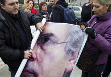 Citizens roll up a poster of Spanish judge Baltazar Garzon after a protest in support of Garzon outside the Supreme Court in Madrid Friday Jan. 13, 2012. Garzon, once widely regarded as Spain's most prominent magistrate, goes on trial Monday Jan. 16 for allegedly ordering illegal wiretaps of conversations between jailed suspects and their lawyers in a corruption probe. (AP Photo/Paul White)