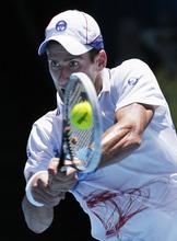 Serbia's Novak Djokovic makes a backhand return to Italy's Paolo Lorenzi during their first round match at the Australian Open tennis championship, in Melbourne, Australia, Tuesday, Jan. 17, 2012. (AP Photo/John Donegan)