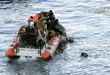 Italian naval divers recover a body from the cruise ship Costa Concordia, Tuesday, Jan. 17, 2012. Italian media say five bodies have been found aboard a cruise ship capsized off the coast of Tuscany, raising the official death toll to 11. Teams have been searching the ship for passengers and crew missing since the Costa Concordia struck rocks Friday evening and capsized. Rescuers exploded four holes in the hull of the ship earlier Tuesday to gain easier access to areas that had not yet been searched. (AP Photo/Gregorio Borgia)
