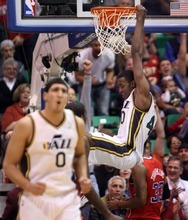 Steve Griffin  |  The Salt Lake Tribune   Utah's Enes Kanter, left, reacts as Jeremy Evans throws down a dunk as the Jazz pull away during second half action of the Utah Jazz versus Los Angeles Clippers game at EnergySolutions Arean in Salt Lake City, Utah  Tuesday, January 17, 2012.