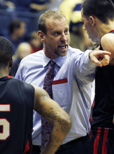 Utah head coach Larry Krystkowiak, center, speaks to players Kareem Storey, left, and Jason Washburn during the first half of an NCAA college basketball game against California, Saturday, Jan. 14, 2012 in Berkeley, Calif. (AP Photo/George Nikitin)