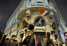 An anti-government protester waves a national flag after he climbed on a building in downtown Bucharest, Romania, Monday, Jan. 16, 2012. Dozens of demonstrators gathered in downtown Bucharest, Monday as Romania's prime minister warned that violent protests that left 59 injured over the weekend could jeopardize stability and economic growth. Police on Sunday clashed with a small contingent of around 1,000 protesters in the capital, after four days of demonstrations against austerity measures turned violent. Tear gas and flares were used to repel demonstrators hurling stones and firebombs.(AP Photo/Octav Ganea)