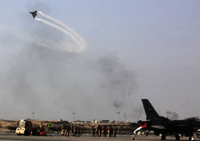 A military aircraft flies through the smoke of tire fires set by anti-government protester during the Bahrain International Airshow in Sakhir, Bahrain,  Thursday, Jan. 19, 2012. Protesters set tire fires on roads nationwide, attempting to darken the skies to make their presence felt during the prestigious air show. (AP Photo/Hasan Jamali)