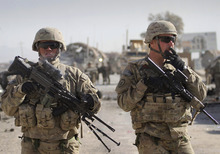 U.S. soldiers with the NATO led International Security Assistance Force (ISAF) stand guard at the scene of a suicide attack in Kandahar south of Kabul, Afghanistan, Thursday, Jan. 19, 2012. (AP Photo/Allauddin Khan)