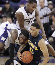 California's Allen Crabbe (23) holds on to the ball as Washington's Tony Wroten, left, and Terrence Ross (31) pile on in the second half of an NCAA college basketball game Thursday, Jan. 19, 2012, in Seattle. California won 69-66. (AP Photo/Elaine Thompson)